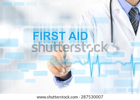 Doctor hand touching FIRST AID (words) sign on virtual screen - stock photo