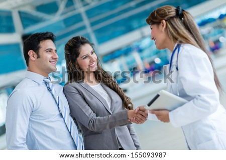Doctor handshaking with a couple at the hospital - stock photo
