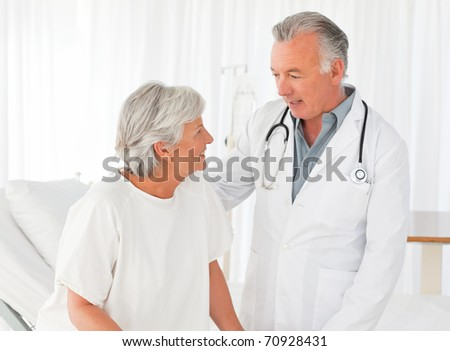 Doctor helping his patient to walk - stock photo