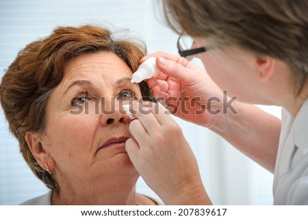Doctor helps the patient and gives the eye drops - stock photo