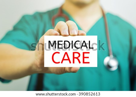 Doctor holding a  business card with capital lettering   MEDICAL CARE in hand,Doctor shows card.Medical and healthcare  concept, medical support and service concept, Selective focus.vintage tone. - stock photo