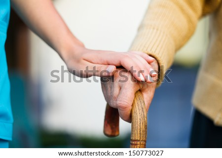Doctor holding a senior patients 's hand on a walking stick - special medical care concept for Alzheimer 's syndrome. - stock photo