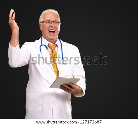 Doctor Holding A Tablet And Happy On Black Background - stock photo