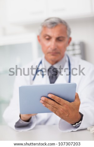 Doctor holding a tablet computer while using it in a medical office - stock photo