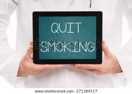 Doctor holding a tablet pc with QUIT SMOKING text on a green Chalkboard screen. - stock photo