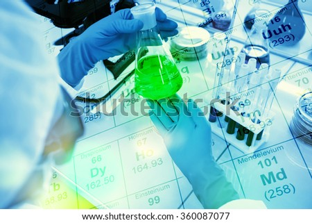 Doctor holding a test tube, a flask with liquid in special laboratory preparing for experiments and treatments - stock photo