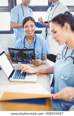 Doctor holding a x-ray report in conference room in hospital - stock photo