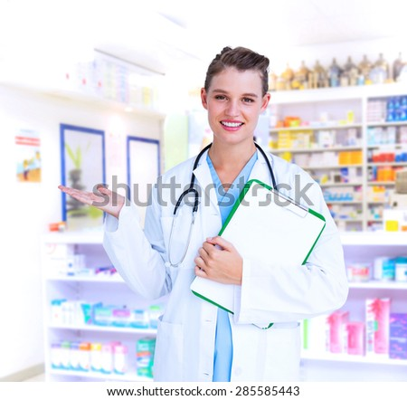 Doctor holding clipboard and presenting with her hand against close up of shelves of drugs - stock photo