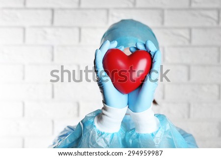 Doctor holding decorative heart on brick wall background - stock photo