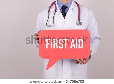 Doctor holding speech bubble with FIRST AID message - stock photo