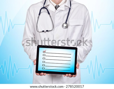 doctor holding touch pad with checklist on a blue background - stock photo