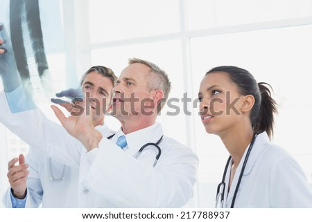Doctor holding up an x-ray with fellow doctors - stock photo