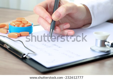 Doctor  in a white labcoat writing out RX prescription - stock photo