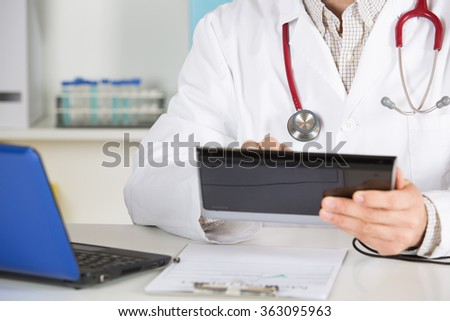 Doctor in consultation ill patient taking notes - stock photo