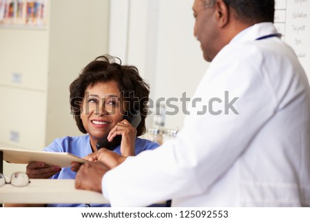 Doctor In Discussion With Nurse At Nurses Station - stock photo