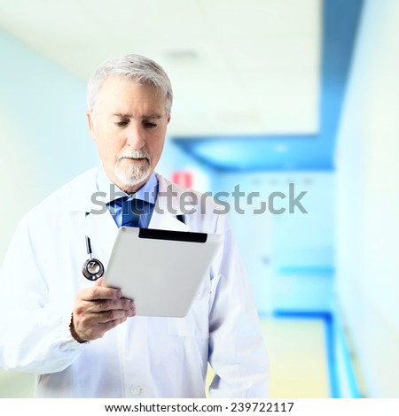 Doctor in the hospital hallway looking at tablet - stock photo