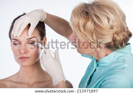 Doctor injecting botox in the forehead, horizontal - stock photo