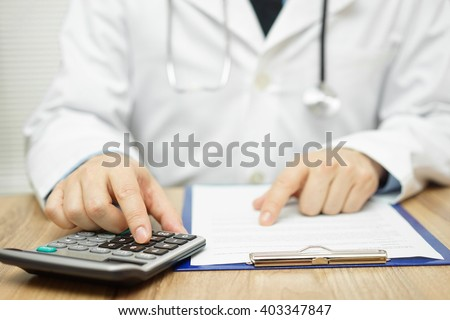 Doctor is using calculator to sum all of expenses - stock photo