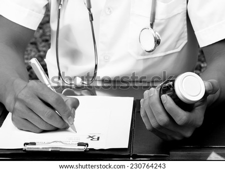 Doctor is writing a prescription, Stethoscope (black &White style) - stock photo