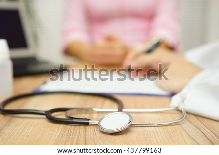 doctor is writing prescription to patient, focus on stethoscope - stock photo