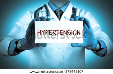 Doctor keeps a card with the name of the diagnosis - hypertension. Selective focus. Medical concept. - stock photo