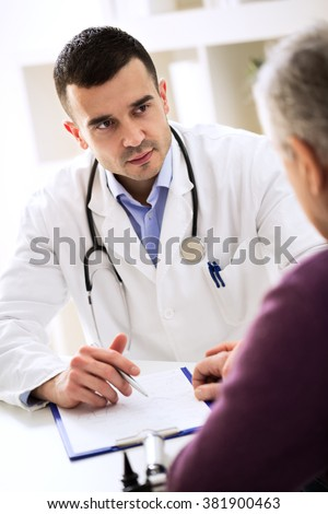 Doctor listening to patient explaining about his painful - stock photo
