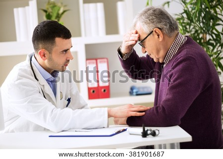 Doctor listening to patient explaining his headache painful - stock photo