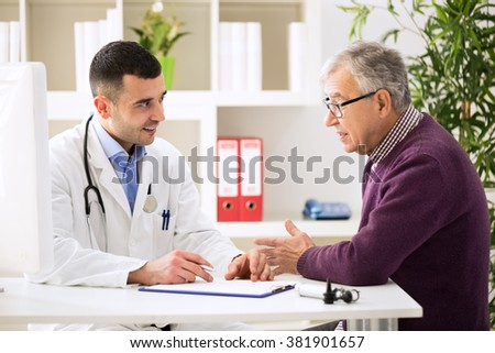 Doctor listening to patient explaining his painful in his office - stock photo