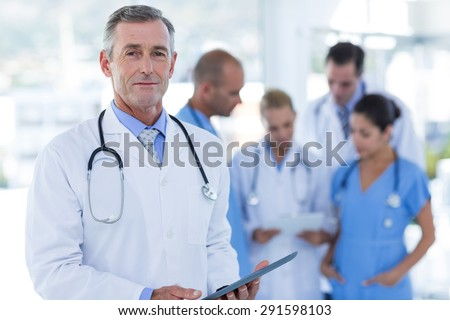 Doctor looking at camera while his colleague discussing in medical office - stock photo