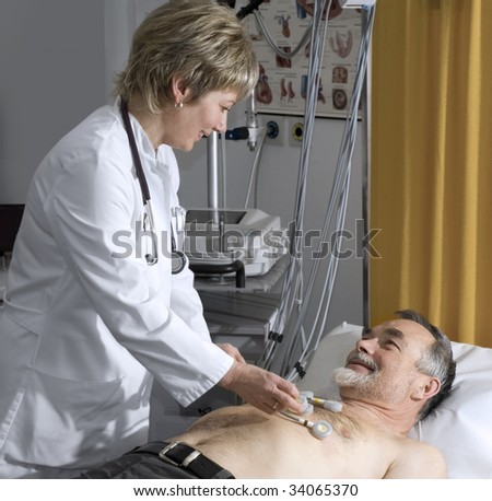 doctor makes the elderly patient ready for  EKG test - stock photo