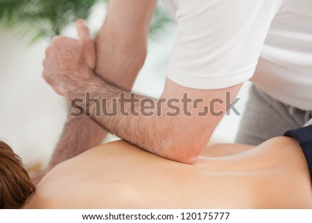 Doctor massaging his back of his patient while using his elbow in a room - stock photo
