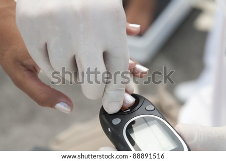 Doctor measuring a patient's blood glucose - stock photo