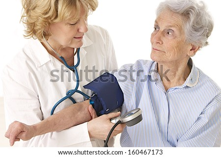 doctor measuring blood pressure of female patient - stock photo