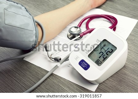 Doctor measuring blood pressure of patient, Digital Blood Pressure Monitor on wood background, Medical equipment, Examining equipment. (Vintage Style Color) - stock photo