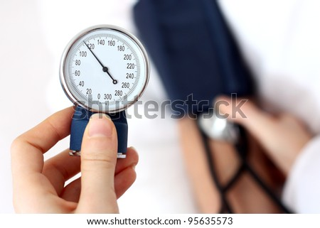 Doctor measuring the blood pressure - stock photo