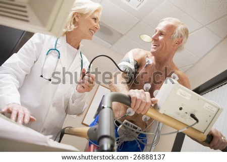 Doctor Monitoring The Heart-Rate Of Patient On A Treadmill - stock photo