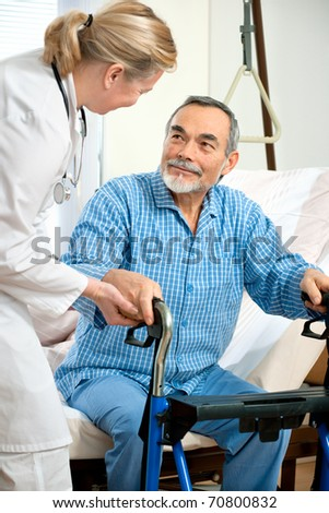 doctor or nurse helps a senior patient to get up in hospital - stock photo