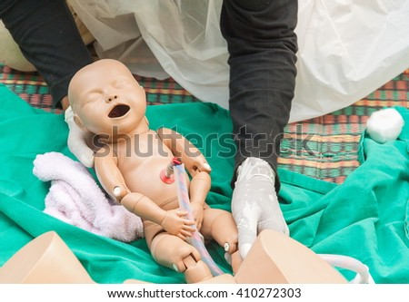 Doctor, paramedic,  The refresher training to assist childbirth newborn with medical baby dummy in emergency the midwife.(select focus baby dummy) - stock photo