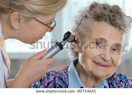Doctor performing ear exam with otoscope on a  senior patient - stock photo