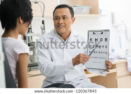 Doctor pointing at eye chart - stock photo