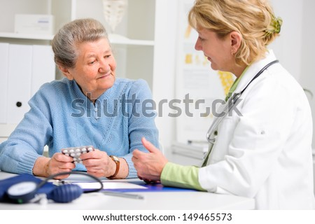 doctor prescribes medication to the senior patient - stock photo