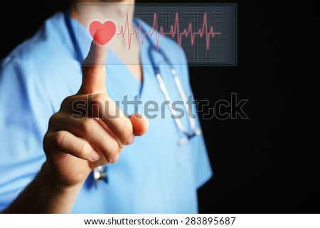 Doctor pressing virtual button with heart diagram - stock photo