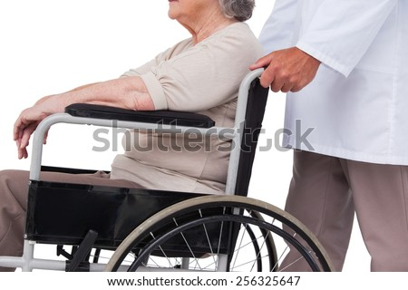 Doctor pushing patient in wheelchair on white background - stock photo