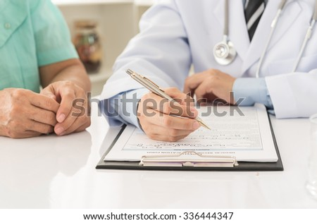doctor record data on application form while consulting patient - stock photo