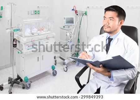 Doctor recording clipboard for diagnosis in newborn in incubator room at hospital  - stock photo