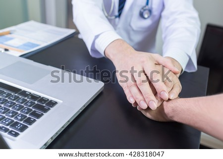 doctor's hands holding  patient's hand for encouragement and empathy - stock photo