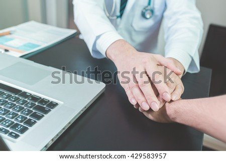doctor's hands holding  patient's hand for encouragement and empathy , vintage tone. - stock photo