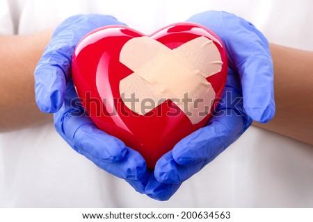 Doctor's hands in blue gloves holding plastered heart - stock photo
