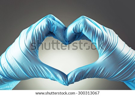 Doctor's hands making heart shape on gray background - stock photo