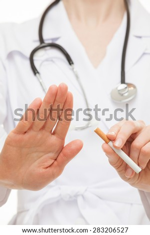 Doctor's hands showing disabling gesture and holding a cigarette, healthy lifestyle concept - stock photo